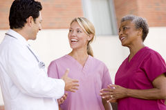 Doctor And Nurses Standing Outside A Hospital. Smiling royalty free stock photo