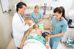 Doctor And Nurses Treating Critical Patient. Doctor and nurses treating critical male patient in hospital stock photo