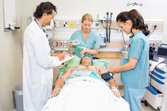 Doctor And Nurses Treating Critical Patient. Doctor and nurses treating critical male patient in hospital stock image