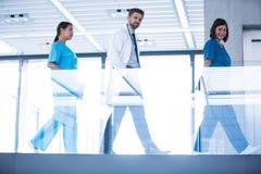 Doctor with nurses walking in corridor Stock Images