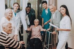 Doctor in Nursing Home. Smiling Patients. Nurse. Medical Staff. Medical Dropper. Sitting Woman. Male. Patient with Walker. Nursing Home. Man with Crutches stock photography