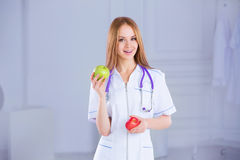 Doctor nutritionist. Confident doctor with apples on the medical background Royalty Free Stock Images