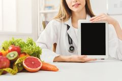 Doctor nutritionist and holding digital tablet. Doctor nutritionist with fruits and holding blank digital tablet, healthy eating and slimming concept. Mockup for Stock Photos