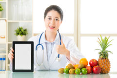 Doctor nutritionist with fruits holding blank digital tablet and Royalty Free Stock Photography