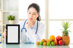 Doctor nutritionist with fruits and holding digital tablet fell Stock Photos