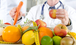 Doctor nutritionist with healthy fruits. Doctor nutritionist in office with healthy fruits Royalty Free Stock Image