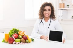 Doctor nutritionist holding blank digital tablet, mockup royalty free stock image