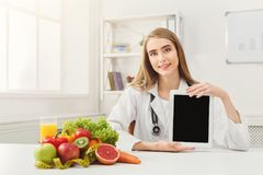 Doctor nutritionist and holding digital tablet. Doctor nutritionist with fruits and holding blank digital tablet, healthy eating and slimming concept. Mockup for Royalty Free Stock Images