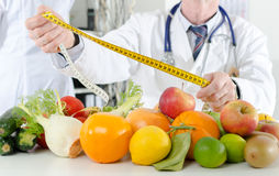 Doctor nutritionist holding a measure tape Royalty Free Stock Photo