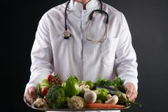 Doctor nutritionist holding a tray of fresh organic vegetables. Health care and medical concept. Healthy eating and Detoxification concept Royalty Free Stock Images