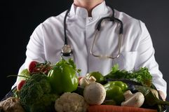 Doctor nutritionist holding tray with heart healthy foods vegetables and fruits. On black background. Healthy food and detox concept Royalty Free Stock Images
