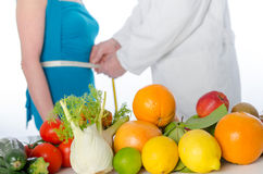 Doctor nutritionist measuring the waist of a patient stock image