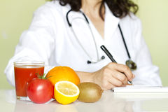 Doctor nutritionist in office with healthy fruits. Diet concept Royalty Free Stock Photo