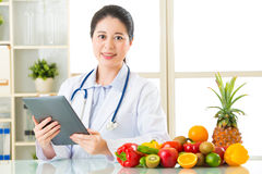 Doctor nutritionist using digital tablet with fruits and vegetab Stock Photos