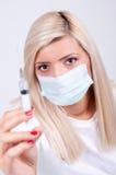 Doctor o enfermera de sexo femenino en la máscara médica que sostiene la jeringuilla con el inje Fotos de archivo