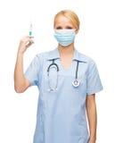 Doctor o enfermera de sexo femenino en la máscara que sostiene la jeringuilla Foto de archivo