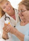Doctor o enfermera de sexo femenino que explica la prescripción al adulto mayor W Imagenes de archivo