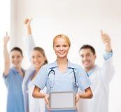 Doctor o enfermera de sexo femenino sonriente con PC de la tableta Imagen de archivo libre de regalías