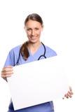 Doctor o enfermera que lleva a cabo un cartel en blanco imagen de archivo libre de regalías