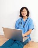 Doctor o enfermera sonriente de la mujer con el ordenador portátil Foto de archivo