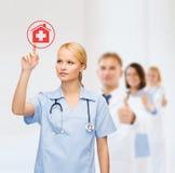 Doctor o enfermera sonriente que señala al icono del hospital Imagen de archivo libre de regalías