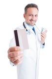 Doctor o médico que muestra la tarjeta de crédito y que sostiene las ampollas Fotografía de archivo