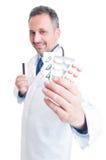 Doctor o médico que muestra las tabletas de la píldora y que sostiene la tarjeta de crédito Fotografía de archivo