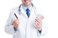 Doctor o médico que sostiene las ampollas de las píldoras y la tarjeta de crédito Imagen de archivo