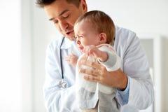 Doctor o pediatra con el bebé gritador en la clínica Foto de archivo