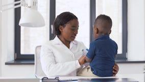 Doctor o pediatra con el paciente del bebé en la clínica almacen de video