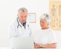 Doctor och hans tålmodig som ser bärbar dator 库存图片