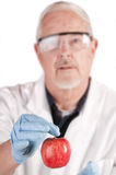 Doctor offering apple. Doctor offering patient an apple with suggestion An apple a day keeps the doctor away stock photo