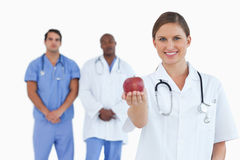 Doctor offering apple with colleagues behind her Stock Photos