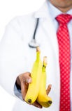 Doctor offering bananas Royalty Free Stock Images