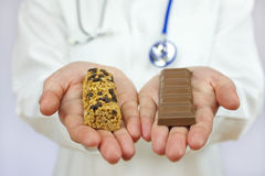 Doctor Offering Granola Bar and Chocolate stock photography