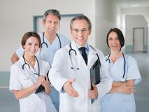 Doctor offering handshake while standing with team in hospital Stock Image