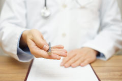 Doctor is offering pen to sign medical document or permission.  royalty free stock images