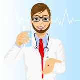 Doctor offering a pill with glass of water Stock Photo