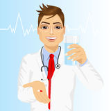 Doctor offering a pill with glass of water Royalty Free Stock Images