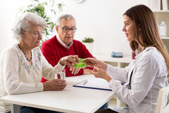 Doctor offering pills senior couple Royalty Free Stock Images