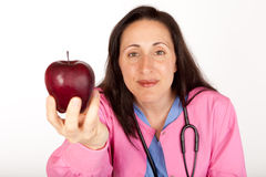 Doctor Offers Apple. Health care provider doctor suggests an apple for healthy living royalty free stock images