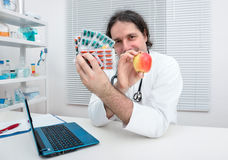 Doctor offers an apple as an alternative to pills Stock Photos
