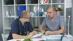 Two doctors men are meeting in the office of the head of the therapy Department.