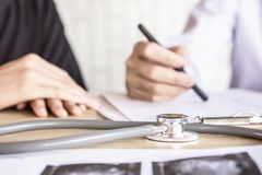 Doctor office desk with stethoscope and radiography royalty free stock photography
