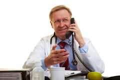 Doctor in office on phone Royalty Free Stock Images
