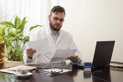 Doctor in the office sitting at a desk and reading medical records. A doctor at work. Doctor in the office sitting at a desk and reading medical records Stock Photography