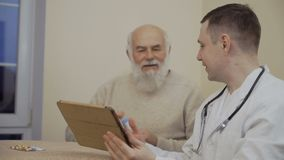 Senior man talking with doctor in clinic. Doctor and old man uses tablet sitting at the table. Therapist shows something to the patient. Senior man holds a jar stock footage