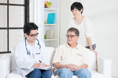 Doctor with old patient. Doctor and patient. Asian senior couple consult family doctor, sitting on sofa. Senior retiree indoors living lifestyle Stock Images
