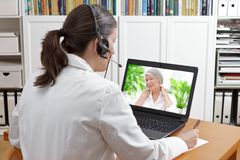 Doctor online call patient shoulder pain. Doctor sitting at the desk of her office with headset and laptop, taking notes during a video call with a patient Royalty Free Stock Photos