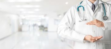 Doctor open hands for your text banner design. Male doctor at hospital opening hand palm to build copy space for your text and design. Medical healthcare stock image